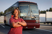 Female bus driver standing in front of a passenger bus