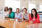 Female business colleagues in an office smiling to camera