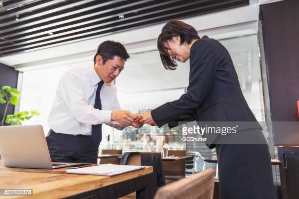 Female business executive handing over her card to the businessman