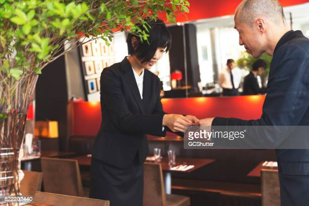 Female business executive respectfully handing over her business card to a client