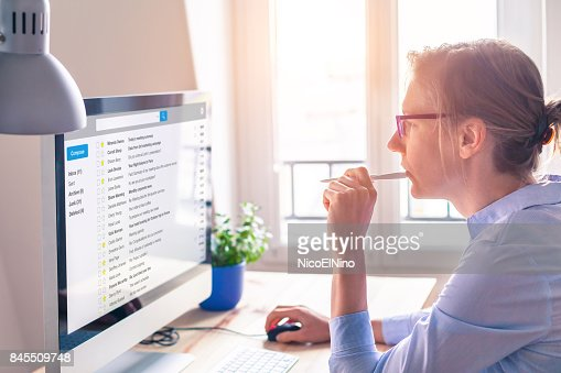 Female business person reading email on computer screen at work : Stock Photo