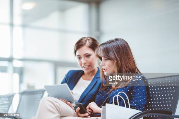 Female business travelers waiting at airport lounge