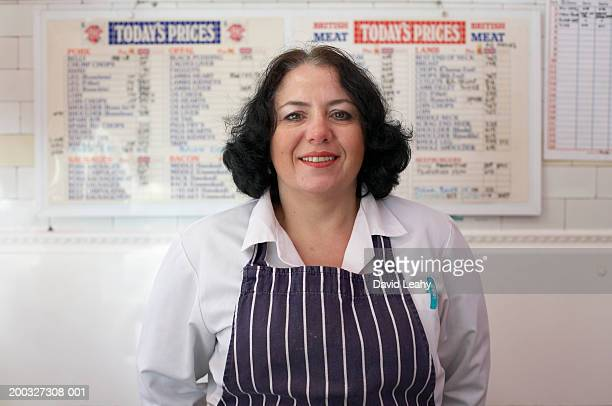 Female butcher wearing apron, smiling, portrait, close-up