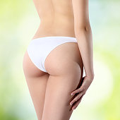 female buttocks in white panties on a green background