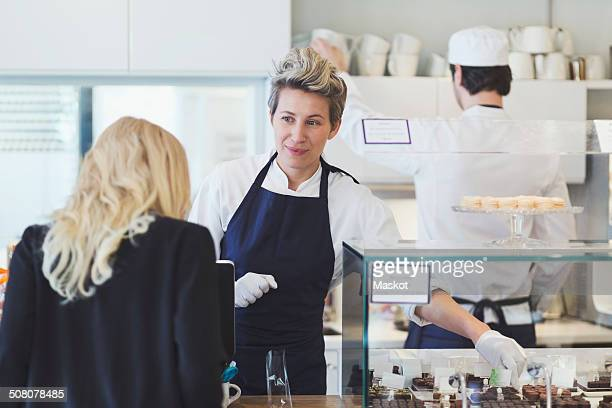 Female cafe worker attending customer at counter