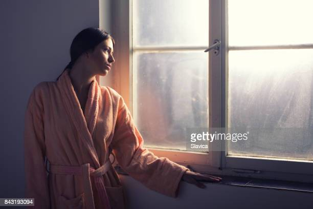 Female cancer patient looking through hospital window