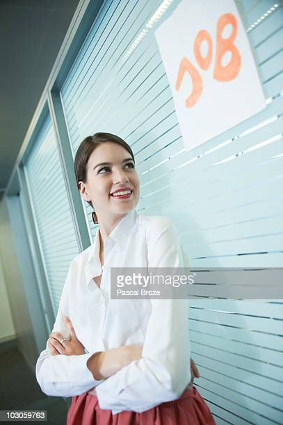 Female candidate waiting outside a cabin for a job interview