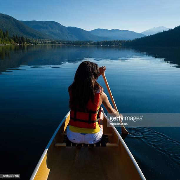 Female canoeing on a prisitine lake