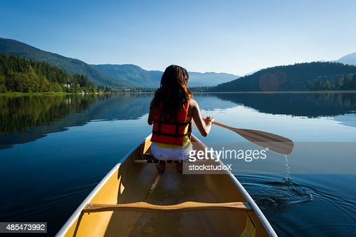 Female canoeing on a prisitine lake