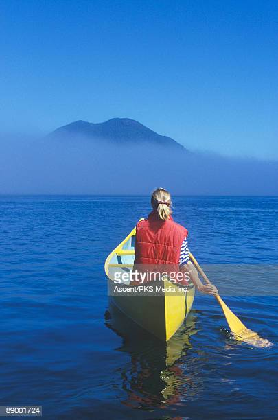 Female canoeist paddles across foggy bay to island