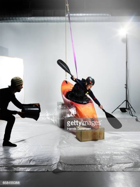 Female canoer being splashed in a studio