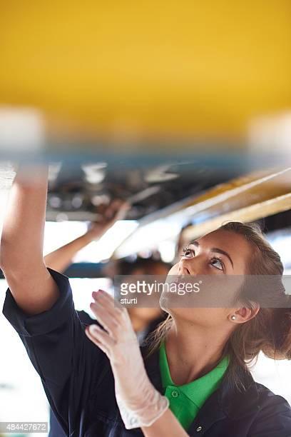 female car mechanics working under a car.