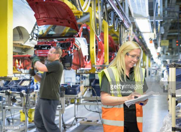 Female car parts inspector on production line in car factory