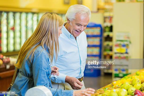 Female caregiver assisting senior man in grocery store