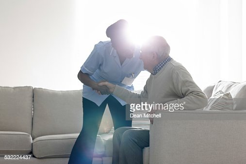 Female caregiver helping senior man get up from sofa