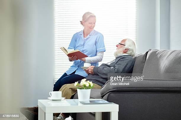 Femme carer tenant un livre assis sur un canapé avec homme senior