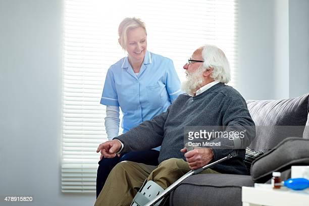 carer avec une femme senior homme assis sur un canapé-lit pour personnes à mobilité réduite
