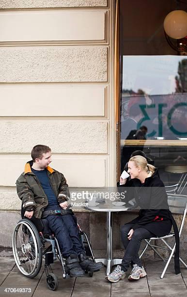 Female caretaker and disabled man having coffee at sidewalk cafe