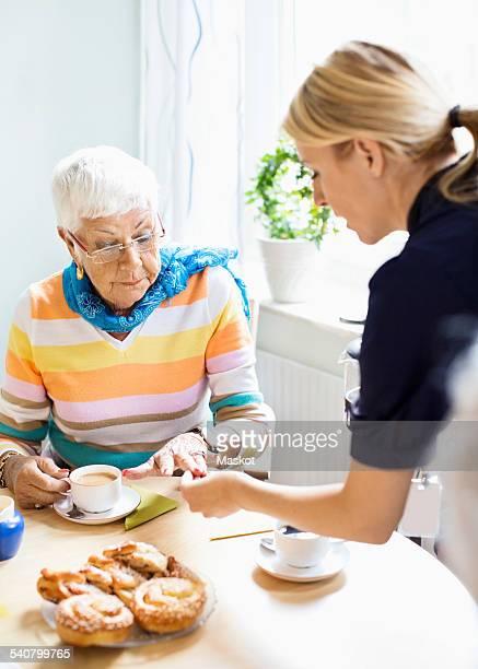 Female caretaker examining senior womans finger at breakfast table in nursing home