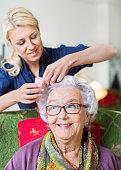 Female caretaker putting curlers to senior womans hair at nursing home