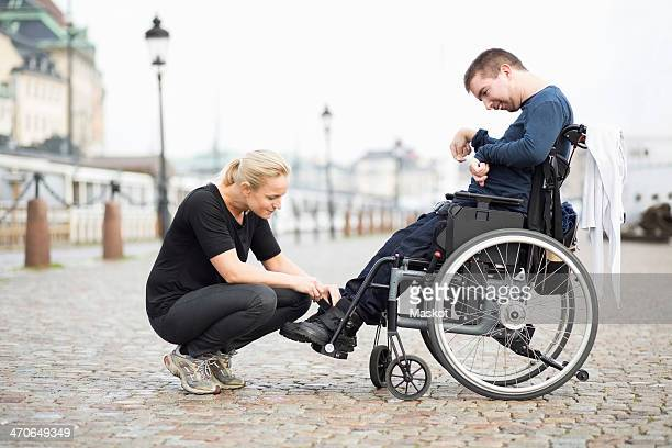 Female caretaker putting on disabled man's shoes on street