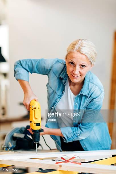Female Carpenter Drilling Plank.