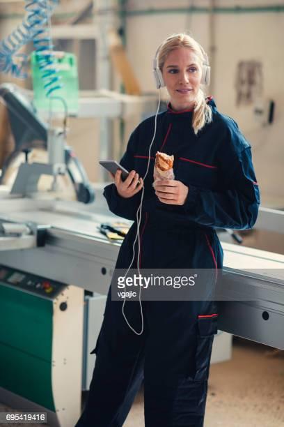 Female Carpenter on Lunch Break In Her Workshop