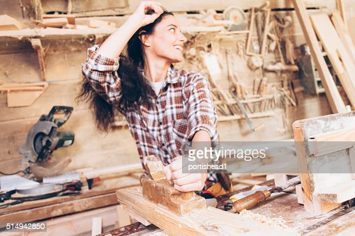 Female carpenter planing wood with a planer at work site