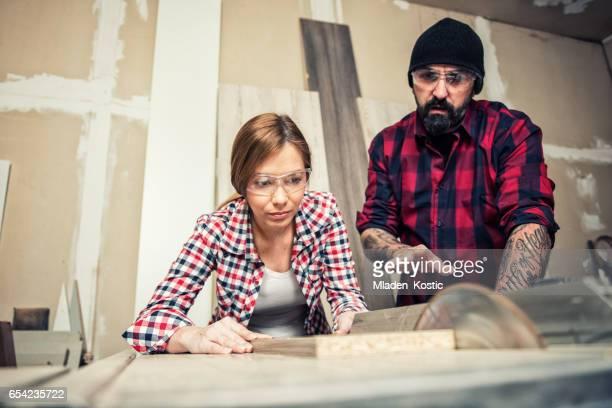 Female carpenter using a circular saw, man helping