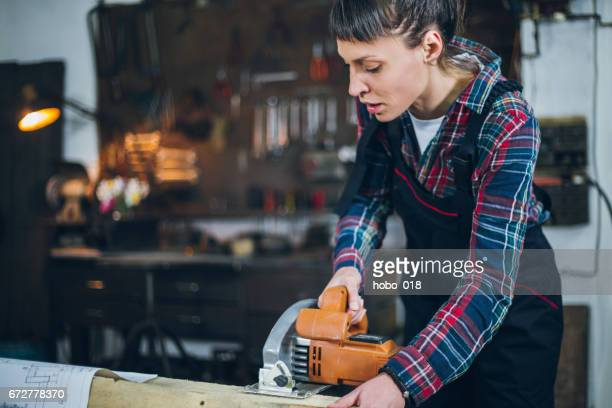 Female carpenter using circular saw