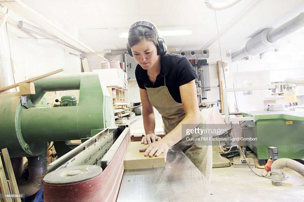 Female carpenter working in workshop : Stock Photo