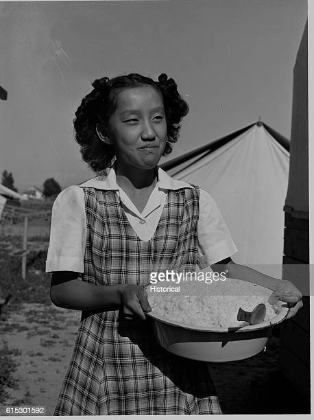 A female carrying a bowl of rice into the cooperative mess hall of the Japanese living at the Farm Security Administration mobile camp in Shelly...