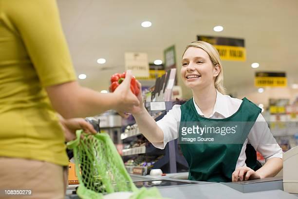 Fêmea caixa e cliente no supermercado finalização da compra