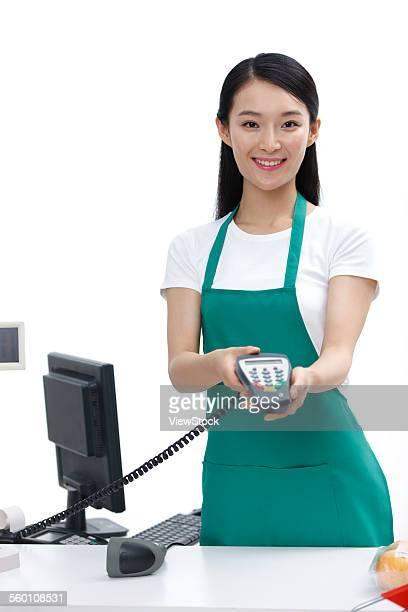 A female cashier holds POS machine