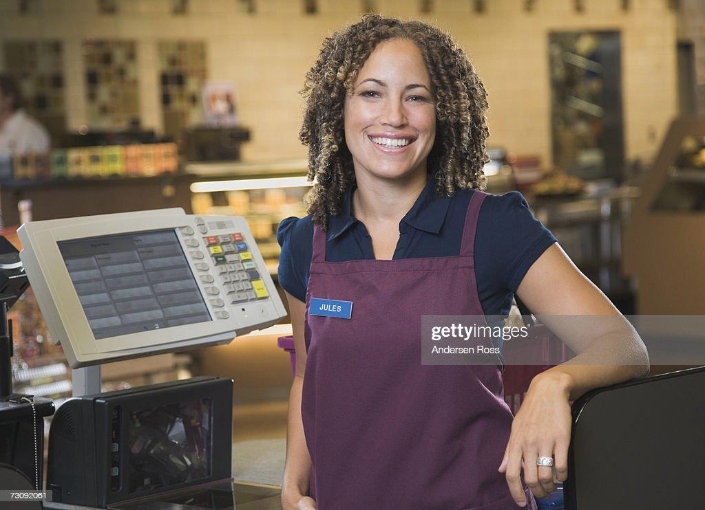 Female cashier smiling, portrait : Stock Photo