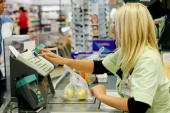 A female cashier weighs apples in a Supermarket on July 27 2005 in Luneburg Germany Sparked by the election manifesto of the opposition party CDU...