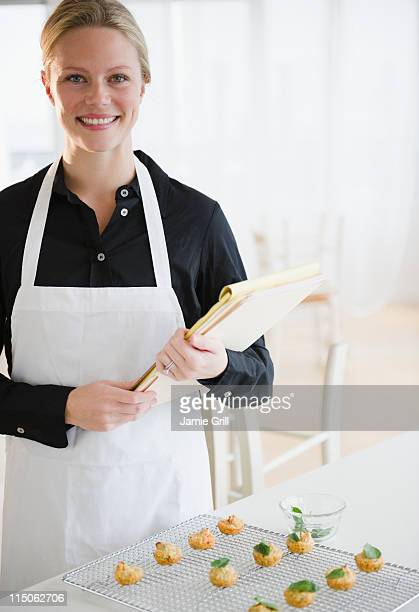Female caterer holding paperwork, smiling
