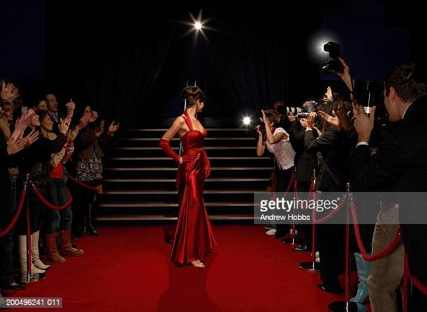 Female celebrity in evening  dress posing for paparazzi on red carpet