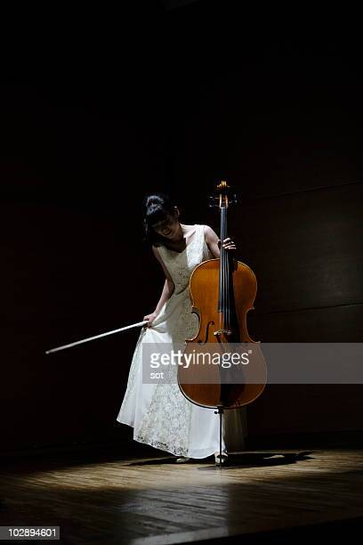 A female cellist making a bow on stage.