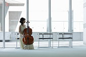 A female cellist making herself at home in lounge.