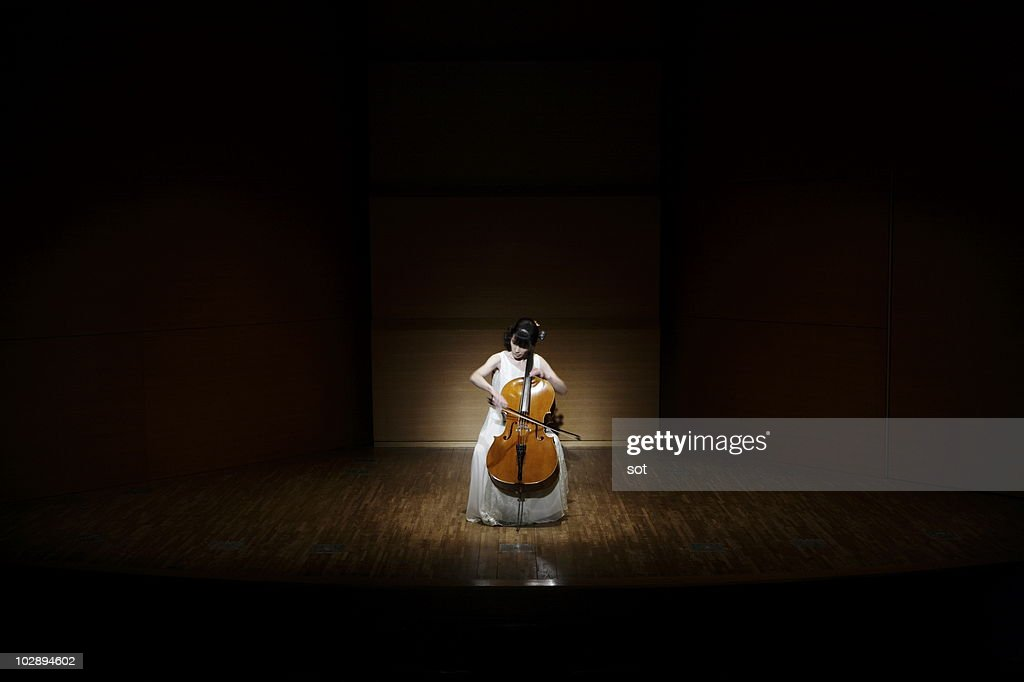A female cellist playing cello on stage. : Stock Photo