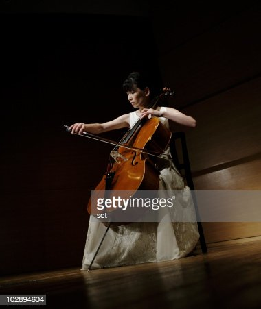 A female cellist playing cello on stage.