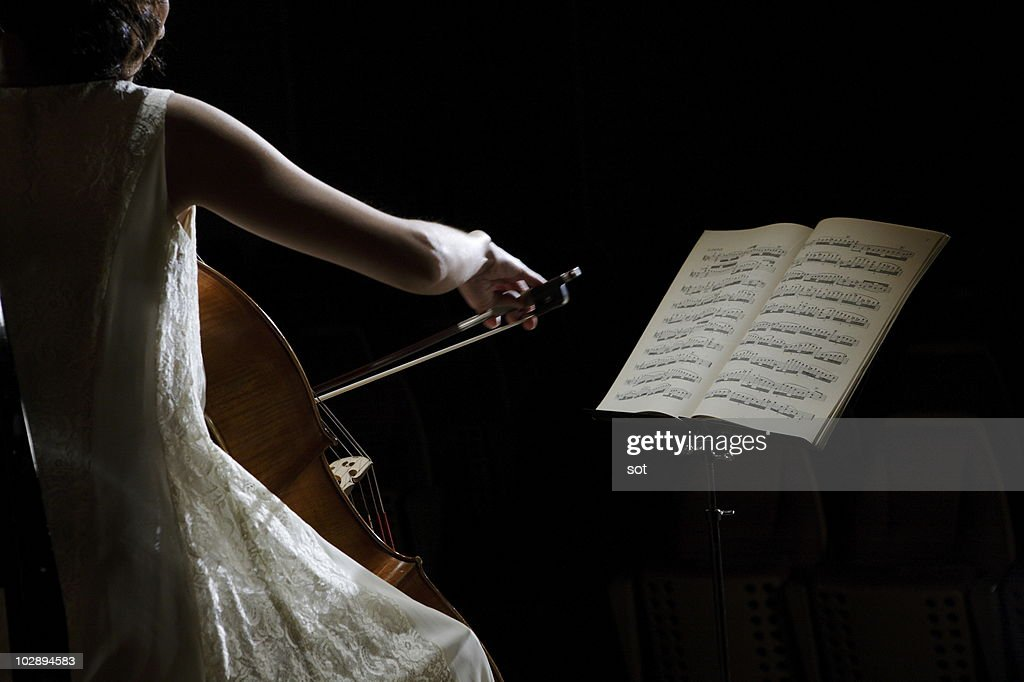 A female cellist playing cello with music stand.