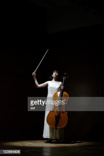 A female cellist raising bow of cello on stage