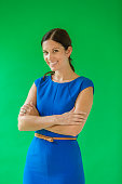 Portrait of a female CEO standing on a chroma key background with her arms folded.