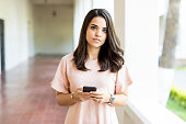 Confident female chatting online using mobile phone while standing in corridor