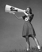 Female cheerleader using megaphone