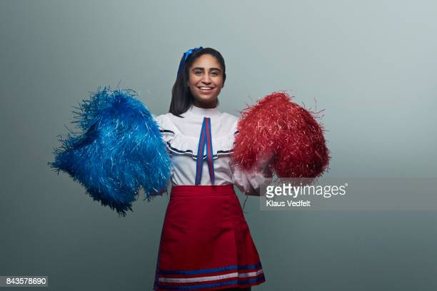 Female Cheerleader with pom poms, laughing to camera