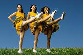 Female cheerleaders doing high kicks