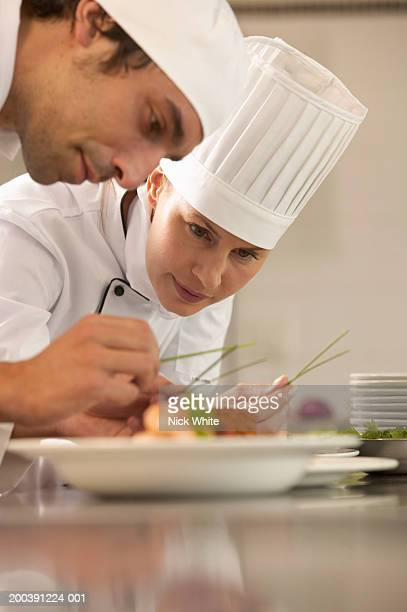Female chef and male cook adding garnish to dishes, low angle view